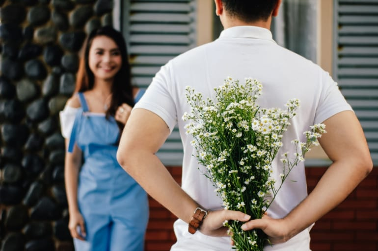 man holding flower for woman