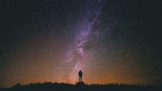 man standing under the galaxy