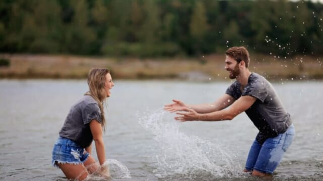 man and woman playing together in the water